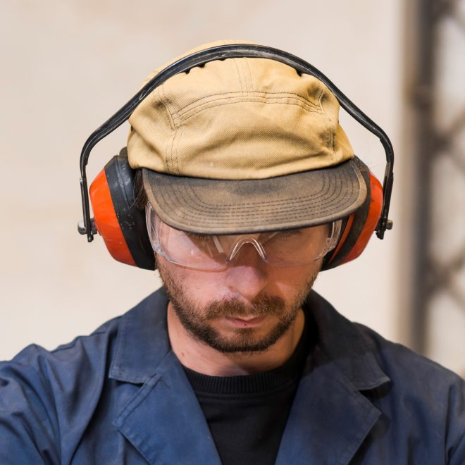 portrait-of-man-wearing-safety-glasses-and-ear-defenders-cutting-wooden-block-on-table-saw