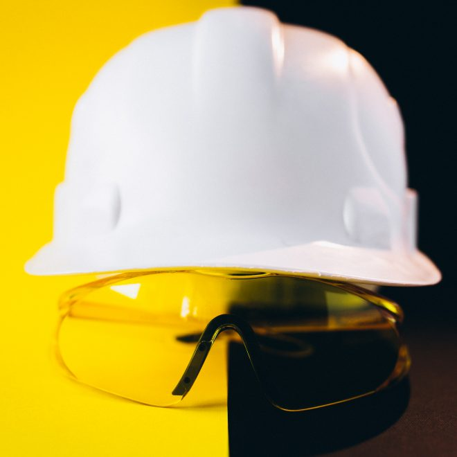 White hard hat with protection eyeglasses isolated on a black and yellow background